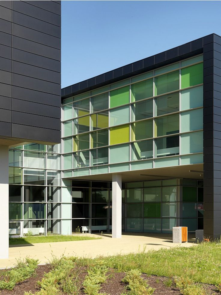 Contrasting elevations, simple forms and eye-catching colors combinations are key features of the new building of Food Technology and Food Service Institute in Łomża, Poland. Dark aluminum facade on the street side contrasts with the glazed courtyards made of green and yellow laminated glass Pilkington Optilam™ I and decorative non-transparent yellow, green and light grey enamelled spandrel glass, that perfectly fit with the surrounding greenery.