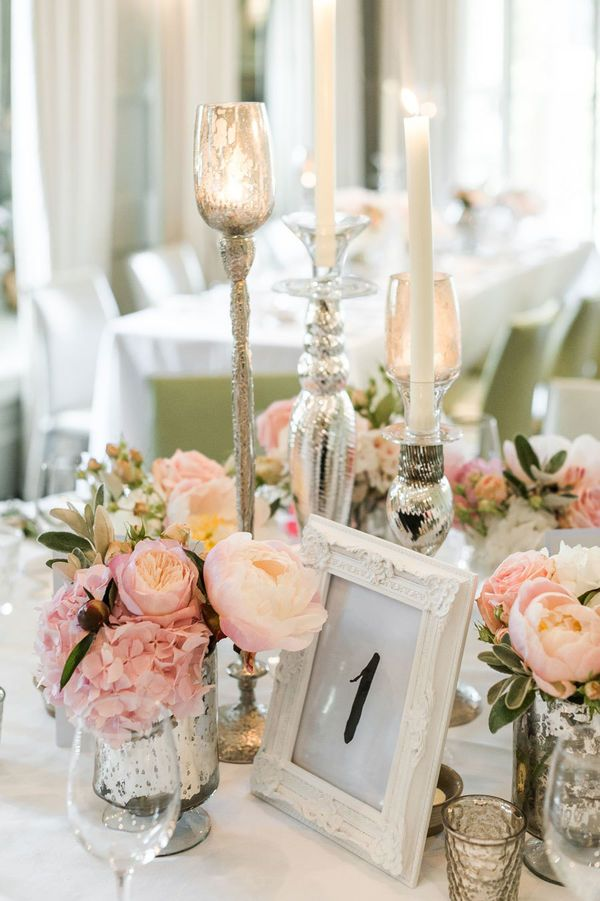 Vintage tablescapes are generally not for the minimalist bride. They are usually laden with unique decor pieces, such as milk glass vases, vintage books, and lace doilies galore. If you want to incorporate some metallic shades into your vintage wedding, try mercury glass. Seen here in the candleholders and votives, they reflect the light beautifully both in the day and evening.