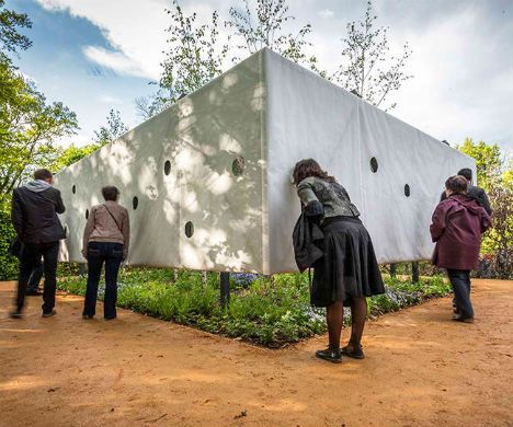 Infinite Garden Multiplies Miniature Forest with Mirrors. Designed by Meir Lobaton Corona and Ulli Heckmann architects, the installation is a white canvas box punctured with circular windows, rendering a small planted area inaccessible. But mirrors mounted inside that box reflect the few trees that are actually contained within it. The effect is enhanced in warm seasons, when the leaves are at their lushest.