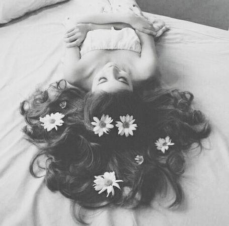 Темноволосая девушка с ромашками на волосах