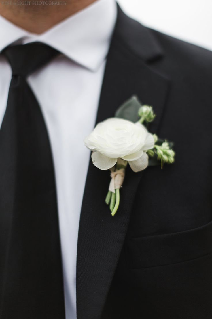 classic groom boutonniere of white ranunculus and larkspur bud.