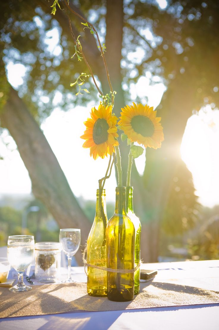 Sunflower and wine bottle centerpieces tied with twine on burlap runner  #sunflowers #rusticwedding