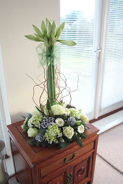 This is a modern Christmas arrangement. It has created spaces and lines, it doesn't use the traditional red and green colour scheme or the traditional plants.