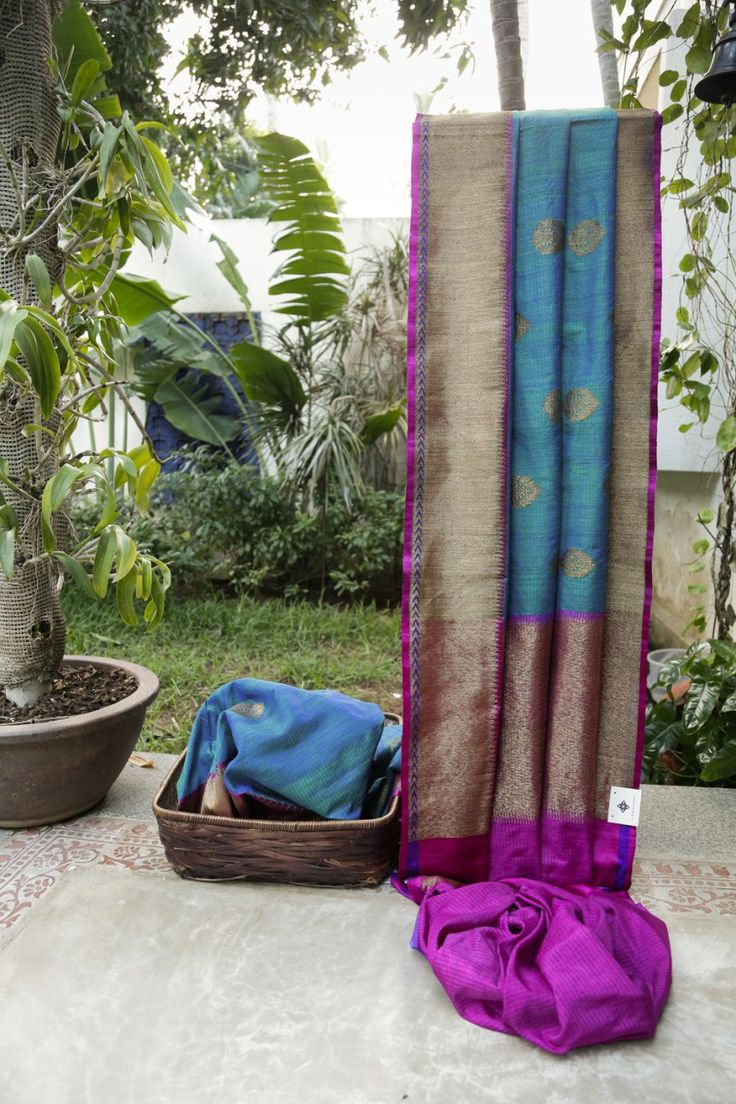 This Aegean blue Benares tussar has green thread work and gold zari bhuttas. The border is in magenta with violet thread work and gold zari work, while the pallu is in magenta, hot pink and gold za…