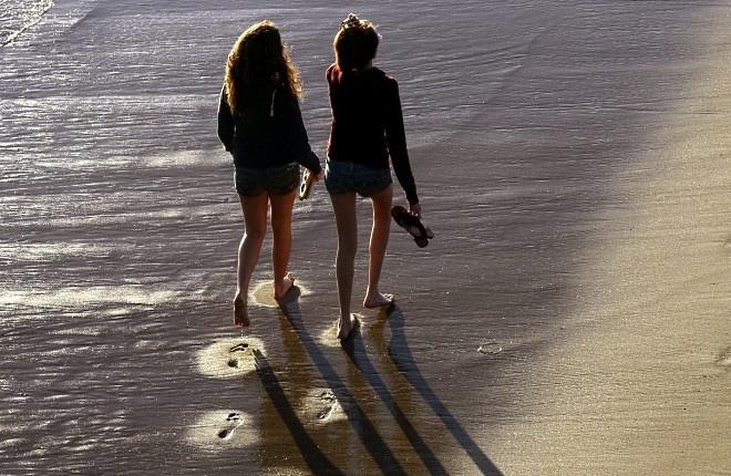 Две момичета се разхождат по плажа на Санта Моника, Калифорния.