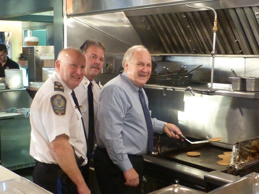 Don't quit your day jobs: Deputy Chief Const. Laurin Stenerson, Fire Chief Tim Armstrong and Mayor Wayne Wright flip some ceremonial pancakes at the Paddlewheeler Pub toy drive and pancake breakfast Wednesday morning. The toys and money collected go to New West Family Place and the Purpose Society.