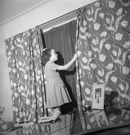 This photo shows how blackout curtains fitted behind ordinary curtains. The girl in this 1943 photo was Doreen Buckner, then aged 7.