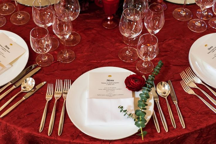 Table decor with red rose and dark red table cloth.