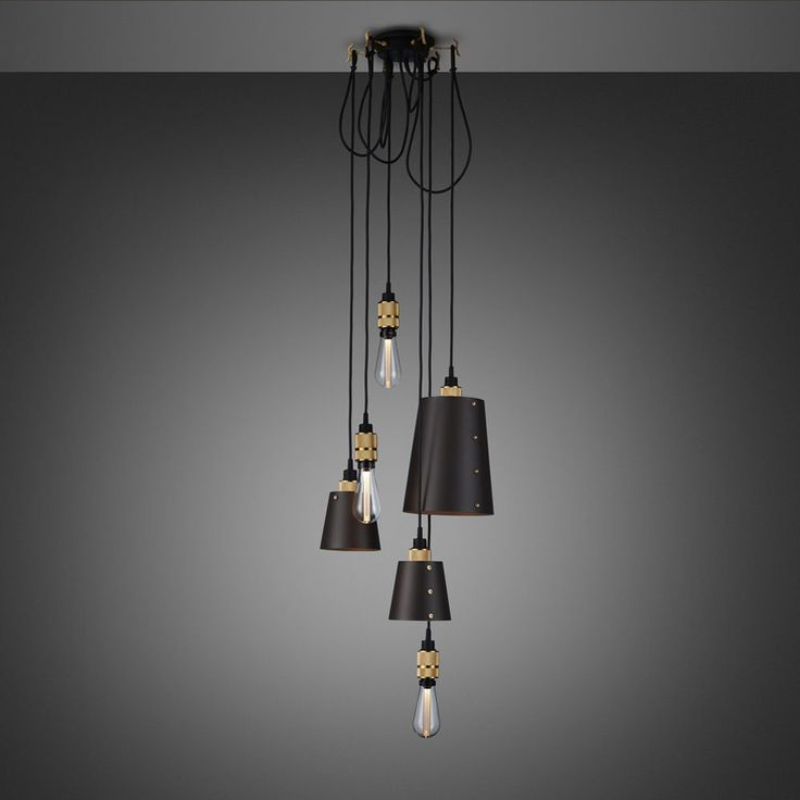A chandelier made up of six brass light pendants each with their own customising hook and matte rubber detailing