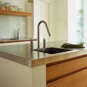 The beautifully designed craftsmanship of GEC Anderson's stainless steel island worktop with square bowl and deep edge fits perfectly in the bespoke luxury kitchen made by Artichoke. High durability with a resilience to heat, fire and sustained heavy use; Totally hygienic composition; Minimal maintenance; Low lifetime costs; 100% recyclability