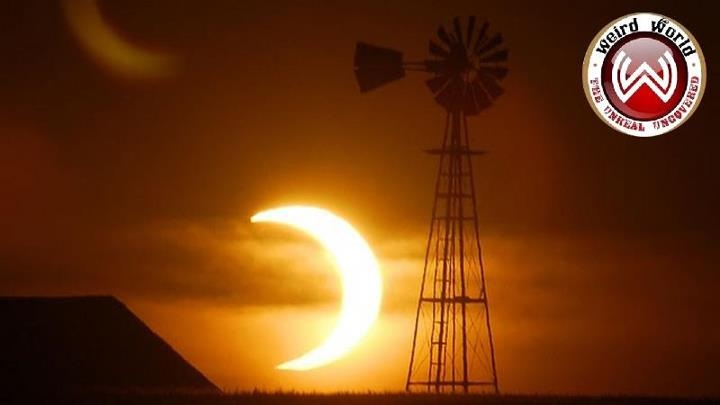 The sun sets behind a barn and windmill on Sunday, May 20, 2012 Annular solar eclipse
