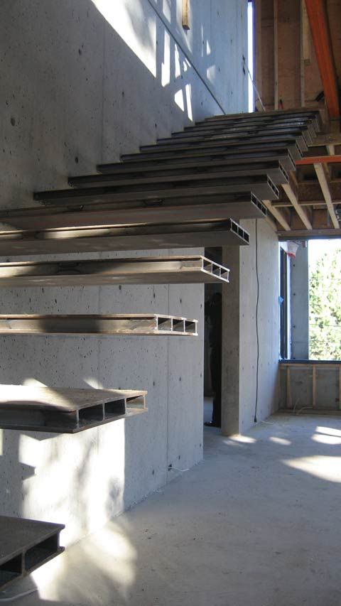 Escalera de diseño volada, de peldaños metálicos. Cantilevered-steel-stair-off-concrete-wall