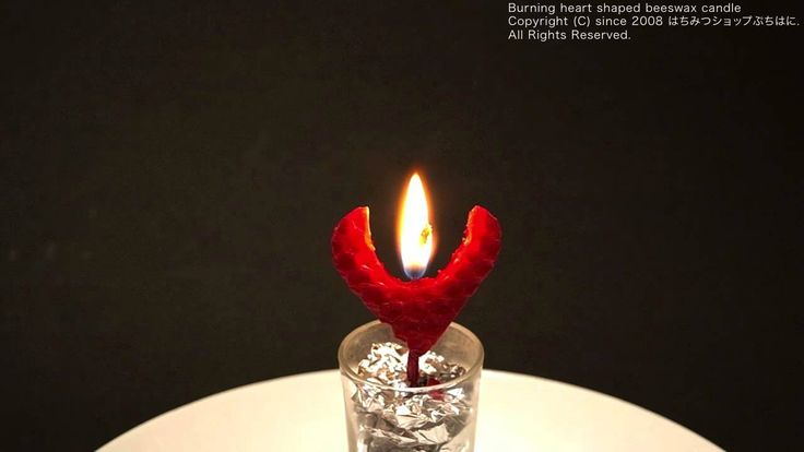 Burning heart shaped beeswax candle