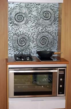 Ammonite pattern in textured, rippled glass, coloured with metallic paint, here in silver and grey. Used in this situation as a splashback.