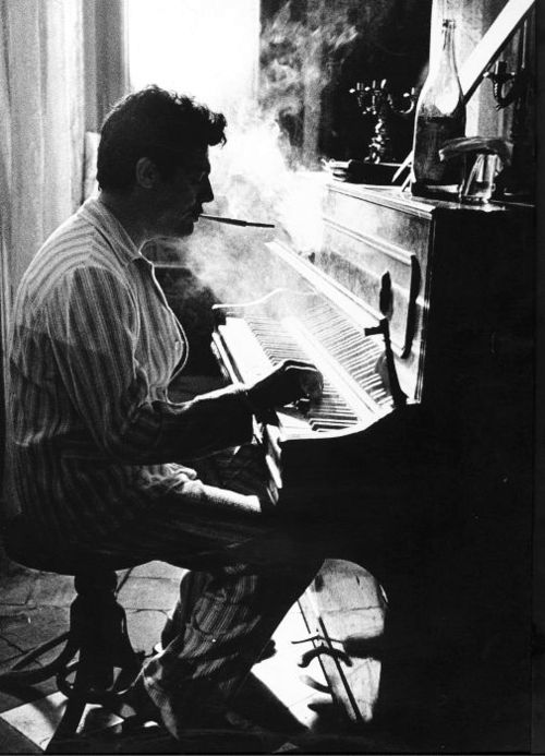 Mastroianni playing piano in pajamas, with cigarette holder.