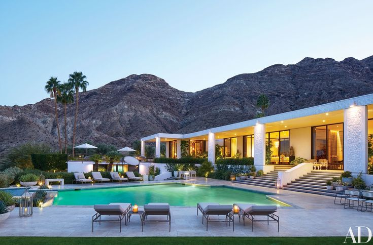 Interior designer Michael S. Smith renovated an early 1970s Howard Lapham house in Rancho Mirage, California, as a weekend retreat to share with his partner, James Costos, the U.S. ambassador to Spain and Andorra. The pool area, offering dramatic views of the desert surroundings, is furnished with custom-made Brown Jordan tables and chaise longues, the latter cushioned in a Kravet fabric.