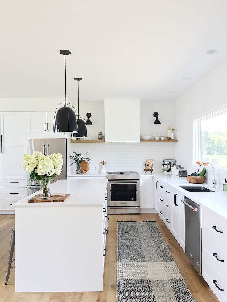 """The entire first floor is centered around the kitchen which features Ikea cabinet bases with Semihandmade fronts painted """"White"""" by Dunn Edwards. The lights by Rejuvenation and Kitchen Aid appliances make this the perfect space for entertaining."""