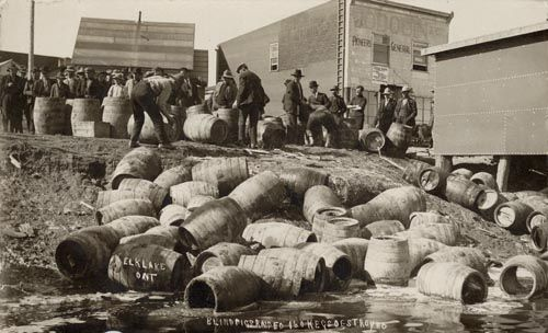 """Blind Pig Raided."" Barrels of alcohol emptied into the lake at Elk Lake, Ontario during Prohibition (c. 1925). #cdnhist"
