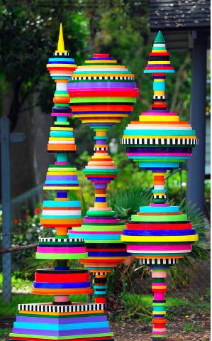Painted and stacked lids, bottle tops and caps. Fun for kids, but would also make great garden art.