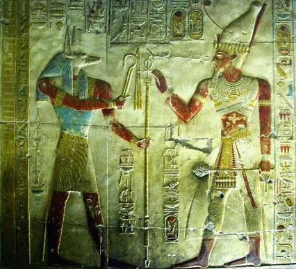 Sur cette œuvre, riche en symboles, Sethi Ier est accompagné d'Anubis. Le pharaon, coiffé du pschent, porte également l'uræus sous forme d'un diadème. La barbe postiche est accrochée à son menton. Dans sa main gauche, la massue kherp et la croix de vie sont présentes. Sa main droite se prépare à recevoir la crosse heka, le flagellum et le sceptre ouas de la part d'Anubis. La fourche de ce dernier sceptre à l'extrémité inférieure est particulièrement bien visible ici.