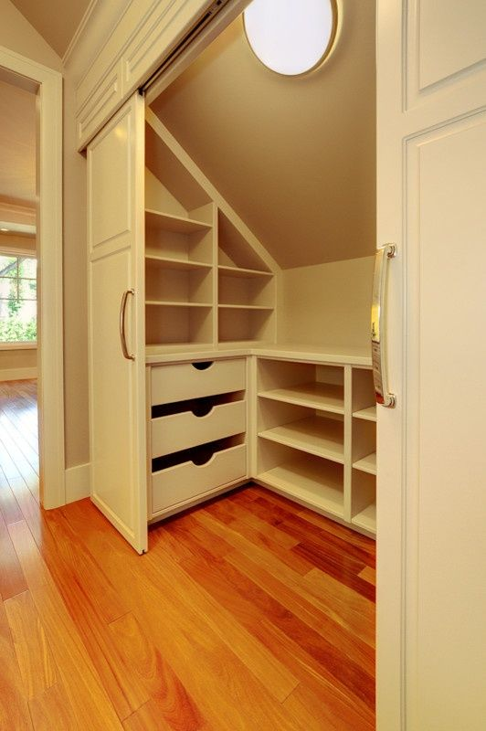 Shelving in a room with a slanted roof.