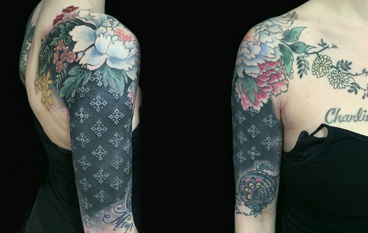 flowers on shoulder, white on black ink tattoo