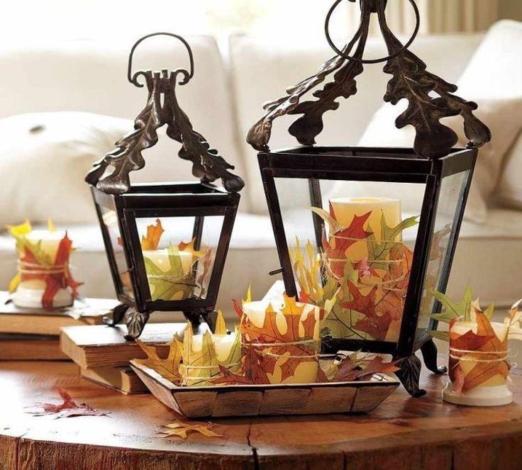 décoration de table automne - lanternes anciennes en métal et verre avec des bougies cylindriques décorées de feuilles d'automne en jaune et vert