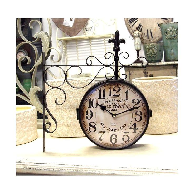 Postarzany zegar dworcowy o metalowej konstrukcji, na górze ozdobiony lilijką.