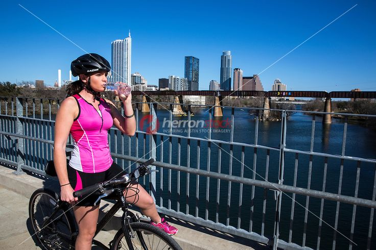 Young attractive female bike cyclist drinks a bottle of water on the Lamar Pedestrian Bridge, overlooking the Austin Skyline on a clear sunn...