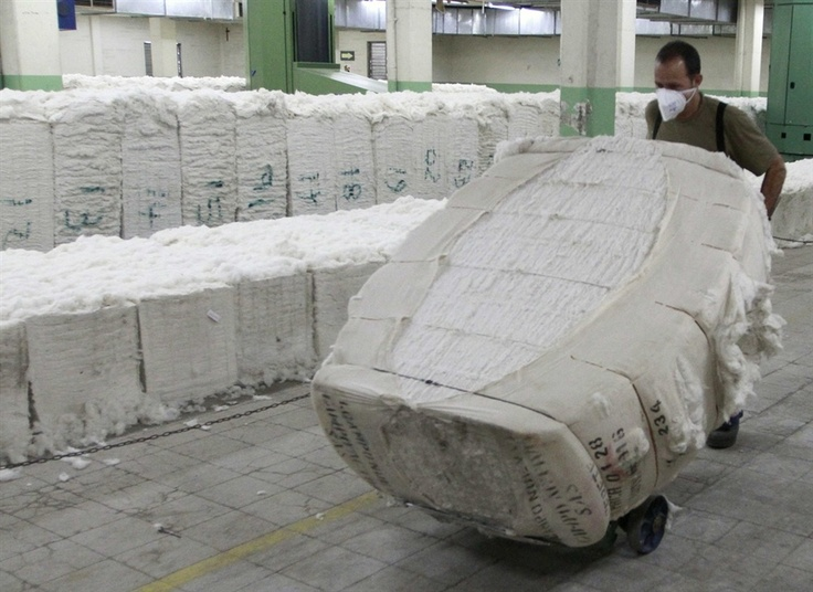 A guy pushing cotton in a textile factory in Colombia which is a big part of Colombian economy