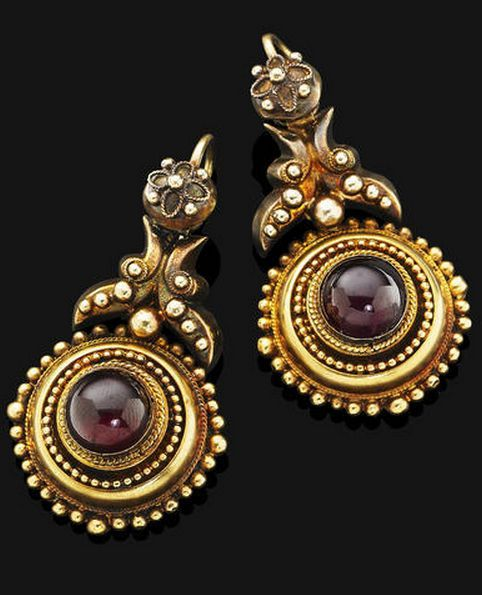 A pair of antique garnet pendent earrings, 1880s Of Etruscan revival design, the central garnet cabochons set within a circular gold plaque of applied ropetwist and bead decoration, suspended from a gold surmount of similar detail, with hook fittings, mounted in 14 carat yellow gold,
