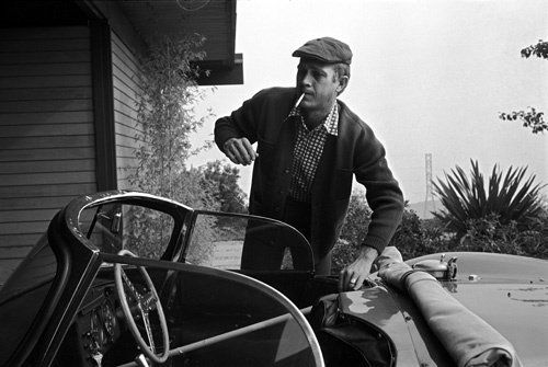 Steve McQueen at his home on Solar Drive warming up his Jaguar XK SS by placing a broomstick on the throttle