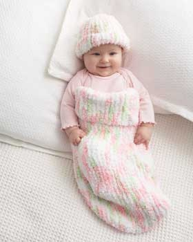 All you need to know is the knit stitch to make this delightful cocoon and matching hat. Shown in Bernat Pipsqueak.
