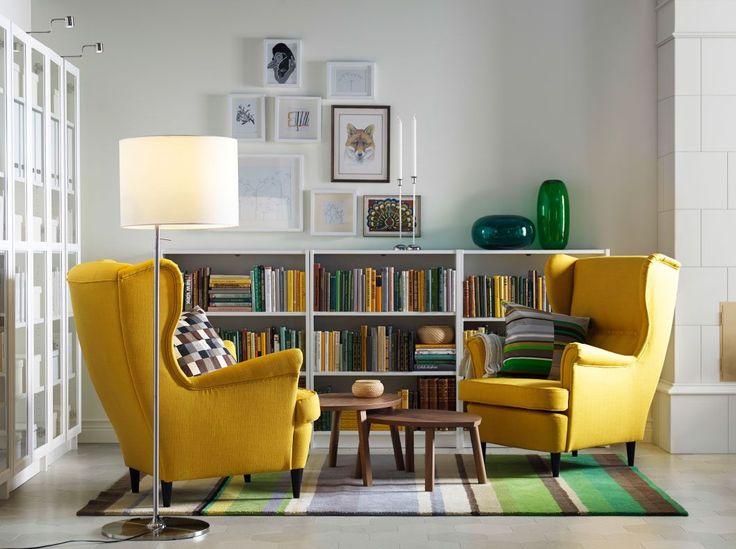 Salón luminoso con dos sillones orejeros amarillos, dos mesas nido de chapa de nogal, unas librerías abiertas blancas y otras con puertas de vidrio.