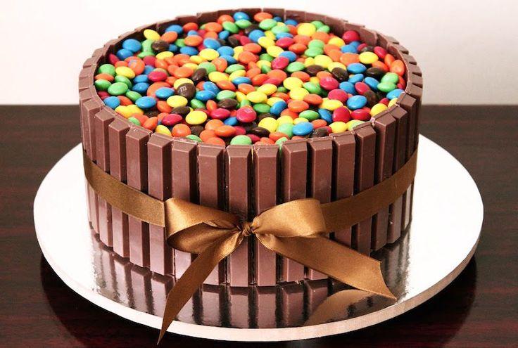 Receita de Bolo Kit Kat, aquele bolo de chocolate, com recheio de chocolate, cercado por chocolates Kit Kat e coberto com m&m's. Quem não vai gostar?