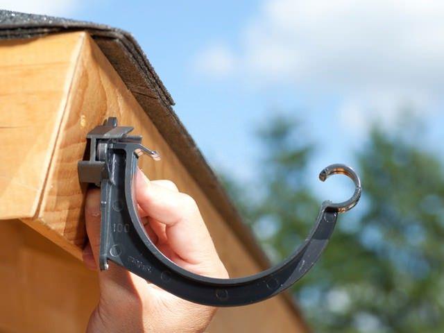 Bei einer abschüssigen Dachabschlußleiste können die mitgelieferte Distanzkeile unter den Rinnenhaltern befestigt werden, damit die Dachrinne gerade aufgehängt werden kann.