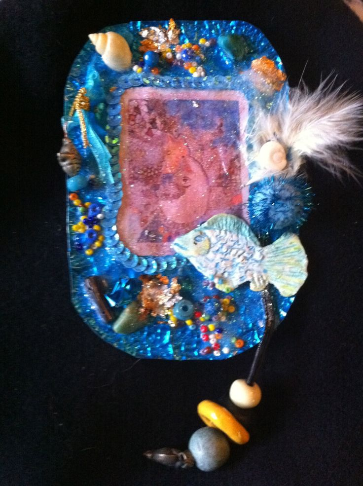 Metal jewellery with shells, beads, sequins, feather, fimo fish & image under resin