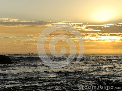 A view of the sun setting over a beach in South Africa.