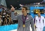 Michael Phelps (Swimming) - Phelps points to the crowd following the podium presentation where he was presented with the gold medal in the Men's 100m Butterfly Final on Day 7 of the London 2012 Olympic Games at the Aquatics Centre