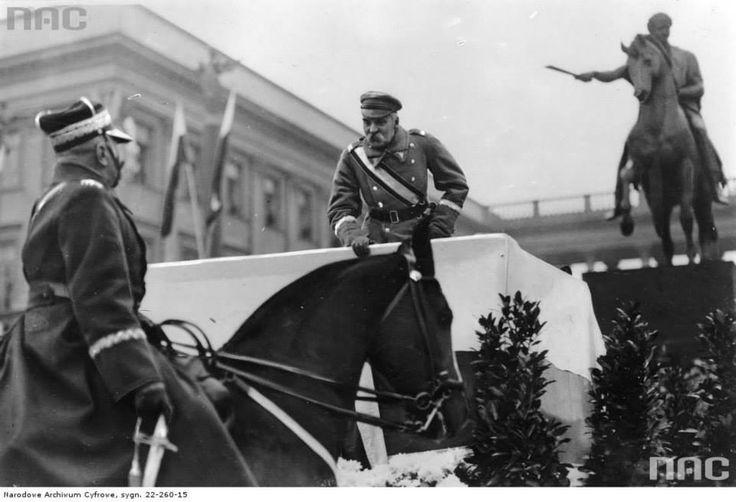 Marszałek Józef Piłsudski na trybunie odbiera raport od wiceministra spraw wojskowych generała Daniela Konarzewskiego na placu Saskim.  Po prawej stronie widoczny pomnik księcia Józefa Poniatowskiego. W tle Pałac Saski. Zródło: NAC