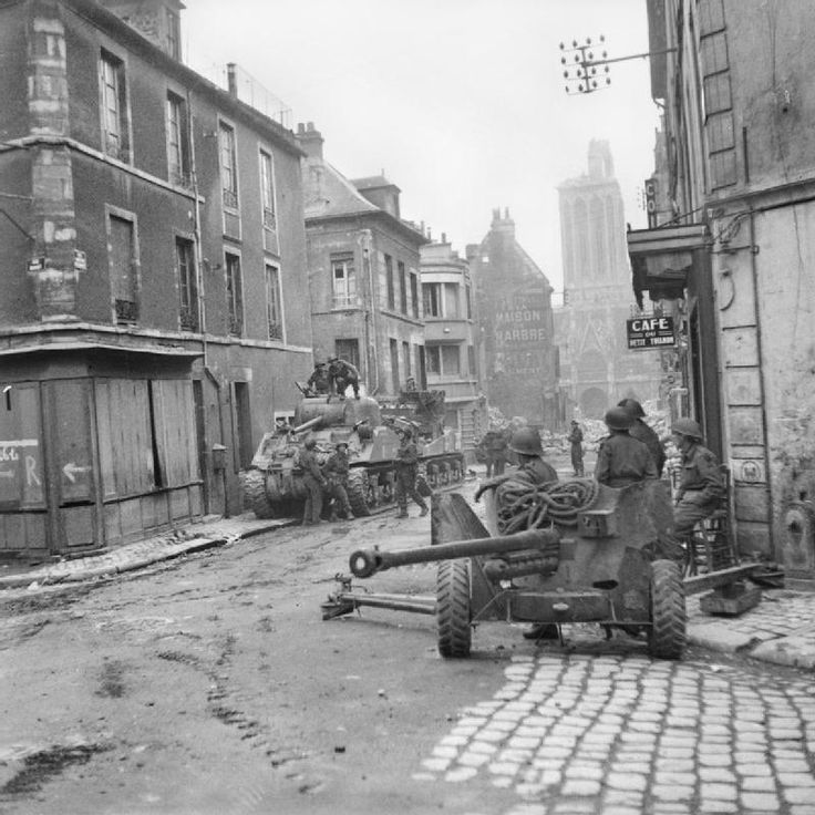 Tanks Sherman et canon antichar Ordnance QF 6 pounder dans la rue Montoir-Poissonnerie, à l'angle avec la Rue du Vaugueux. Caen, 10 juillet 1944.