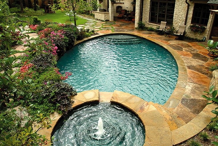 Pool and spa with stone decking  An elevated spa allows water to cascade into the pool, edged with flowing, lush vegetation and Oklahoma stone coping. The pool and spa are surrounded by a patio and stepping stones of textured and stained concrete.