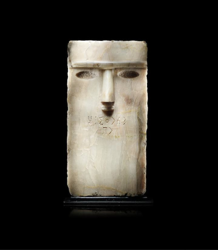 South Arabian alabaster anthropomorphic inscribed stele, 1st century B.C.-1st century A.D. Of rectangular form, the face with stylised features including a long, prominent nose and small pursed mouth sculpted in raised relief, and large almond-shaped eyes recessed once for inlay, below a heavy horizontal ridged browline, the top, sides, and back of the head roughly finished, inscribed in Qatabanian for the deceased below the mouth, 38.7 cm high. Private collection