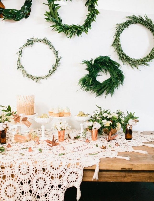 An assortment of wreaths of greenery in differing textures adds a contrasting element to this copper-accented dessert table.