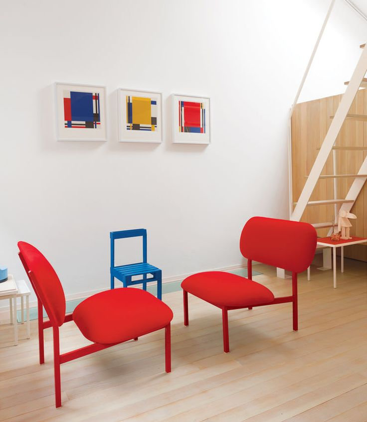 Modern living space with matching red castoff chairs