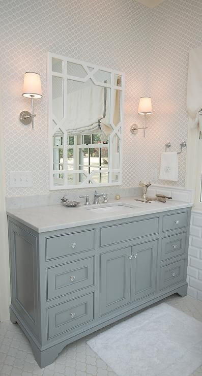 Elegant bathroom features upper walls clad in gray print wallpaper and lower walls clad in white beveled subway tiles lined with a gray vanity topped with carrera marble under a white trellis mirror, Worlds Away Vero White Lacquer Trellis Mirror, illuminated by Thomas O'Brien Bryant Sconces atop a white arabesque Tile floor.