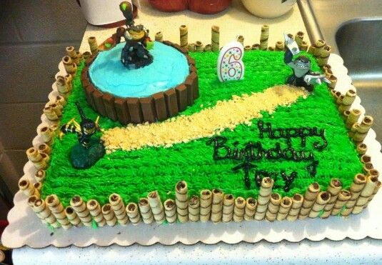 "Skylanders Birthday Cake -- I think this is the one I will attempt.  I can order a sheet cake from Sam's Club with green grass frosting, then decorate it myself, including a circular ""portal of power"" cake on top."