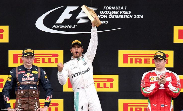Lewis Hamilton celebrates with the winners' trophy, with Max Verstappen second for Red Bul...
