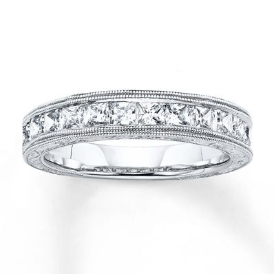 Sparkling princess-cut diamonds totaling 1 carat in weight line the center of this captivating anniversary band for her. Delicate milgrain detail provides textural contrast above and below the diamonds to complete the look. The ring is crafted of 14K white gold. Diamond Total Carat Weight may range from .95 - 1.11 carats.