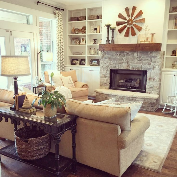 Love the shiplap on the fireplace in this recently renovated client project. White painted built ins, neutral color scheme, and farmhouse accessories lend to the cozy feel of this room.